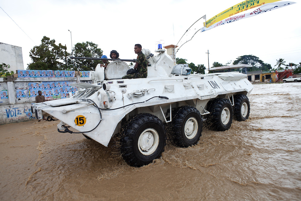 A UN vehicle with soldiers drive on a road flooded by rain from hurricane Tomas.