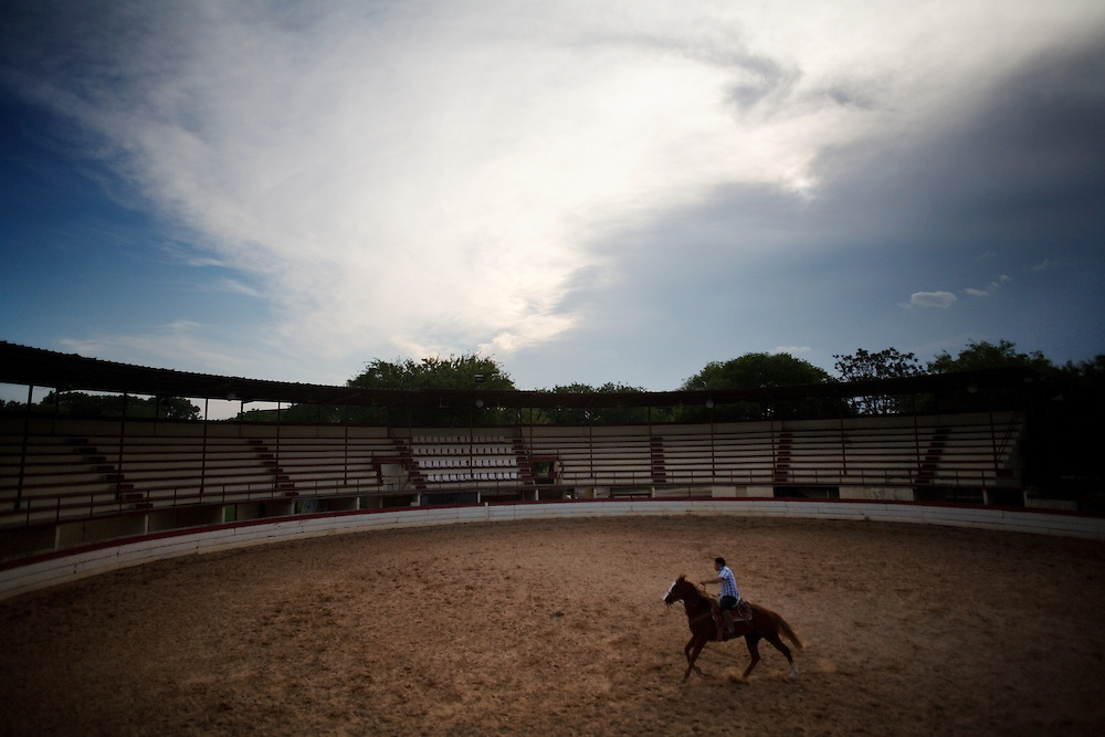 "Central Texas Charreria - Story Summary. The rodeo tradition called charreada began in 16th century Spanish colonial Mexico as a celebration that marked the close of a major cattle round-up. Teams of cowboys, called charros, competed against each other in events of horsemanship and roping skills.  ..The tradition continues today with more than 200 official charreada teams in the United States, 30 of those in Texas, preserving the technique and style of the historic Mexican charro.  Teams compete each weekend in different homemade arenas, called lienzos.  No cash prizes are awarded, just the respect of fellow charros...""Keep the money, keep the belt buckle, we just want the bragging rights,"" says Juan Gonzalez, President of the San Antonio Charro Association...----..A charro trains his horse in an empty lienzo in San Antonio, Texas.  Popular south of the border, charreada in Texas is a sparsely attended event with mostly family and other charro teams in attendance.  ..""We're all amateurs,"" says Juan Gonzalez, ""but there's a passion behind what we do.""  During the week, these men are doctors and lawyers, butchers and carpenters, but on Sunday they become the charro."