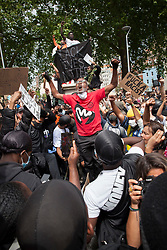**Previously unseen pictures**<br /> © Licensed to London News Pictures; 07/06/2020; Bristol, UK. Protesters celebrate and climb on to the empty pedestal where a statue of Edward Colston was pulled down with a rope during a Black Lives Matter march through the city centre. The death of George Floyd, who died after being restrained by a police officer In Minneapolis, Minnesota, caused rioting and looting across the U.S.A and protests across the world. Photo credit: Mark Simmons/LNP.