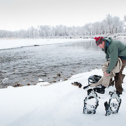 A fly fisherman dons his waders after snowshoeing to a likely looking trout run on the South Fork of the Snake River