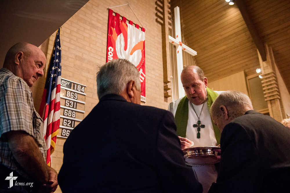 The Rev. Bill Qualman, pastor at Mt. Calvary Lutheran Church, La Grange, Texas, distributes the Sacrament during Divine Service at the church on Sunday, Sept. 3, 2017. Last week, only a handful of church members who weren't trapped by the floodwaters made it to worship. A week after Hurricane Harvey the pews filled up again after the waters receded. LCMS Communications/Erik M. Lunsford