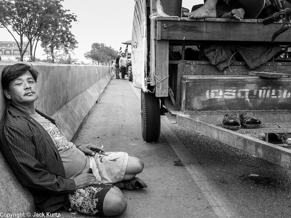 21 FEBRUARY 2014 - KHLONG CHIK, PHRA NAKHON SI AYUTTHAYA, THAILAND: A Thai farmer smokes a cigarette on the highway south of Ayutthaya. About 10,000 Thai rice farmers, traveling in nearly 1,000 tractors and farm vehicles, blocked Highway 32 near Bang Pa In in Phra Nakhon Si Ayutthaya province. The farmers were traveling to the airport in Bangkok to protest against the government because they haven't been paid for rice the government bought from them last year. The farmers turned around and went home after they met with government officials who promised to pay the farmers next week. This is the latest blow to the government of Yingluck Shinawatra which is confronting protests led by anti-government groups, legal challenges from the anti-corruption commission and expanding protests from farmers who haven't been paid for rice the government bought.    PHOTO BY JACK KURTZ