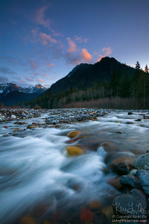 The Carbon River cascades over volcanic rocks left by Mount Rainier's most recent eruption. A dramatic sunset makes Mother Mountain, also located in Mount Rainier National Park, Washington, appear as if it is erupting.