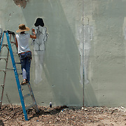 Argentinian street artist Hyuro working on her black-and-white series representating a morphing woman. Living Walls, Atlanta, 2012