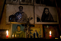 Pictures from the Legion Maria church hang in the home of a midwife in Mathare, a poor slum in Nairobi, Kenya.  Most women in Mathare can not afford to go to a hospital to give birth; they can not even afford the 10 minute taxi ride to get there.  The expecting mothers have no prenatal care and arrive to the midwives' homes once labor has already begun.  The midwives have no supplies and are usually have no formal training.  The mothers often give birth on dirt floors with no medicine, and their babies' unbilical cords are cut with dirty scissors and they are washed with tap water.