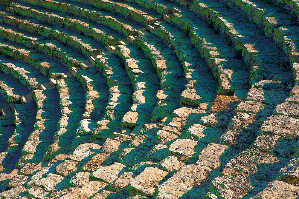 Sicily : ancient Greek Theater at Segesta, 3d century BC. Shadow patterns on the stone seats and stairs have been saturated somewhat to bring out the cyans and reds in the stone.  The graphic composition is a pattern of parallel curves.  The theater is still used for performances .