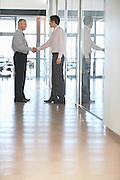Two Businessmen Meeting in Corridor