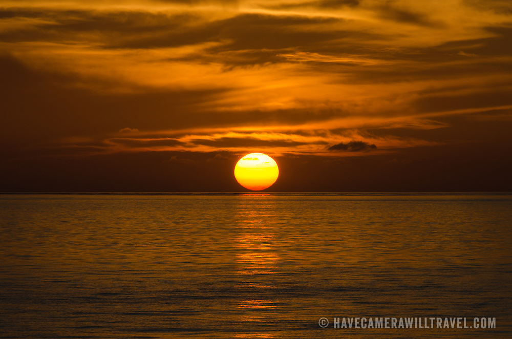 The sun first touched the horizon, create a beautiful golden glow on the water and the light, wispy clouds above. Taken at Swains Reef on the southern end of the Great Barrier Reef of the coast of Queensland, Australia.