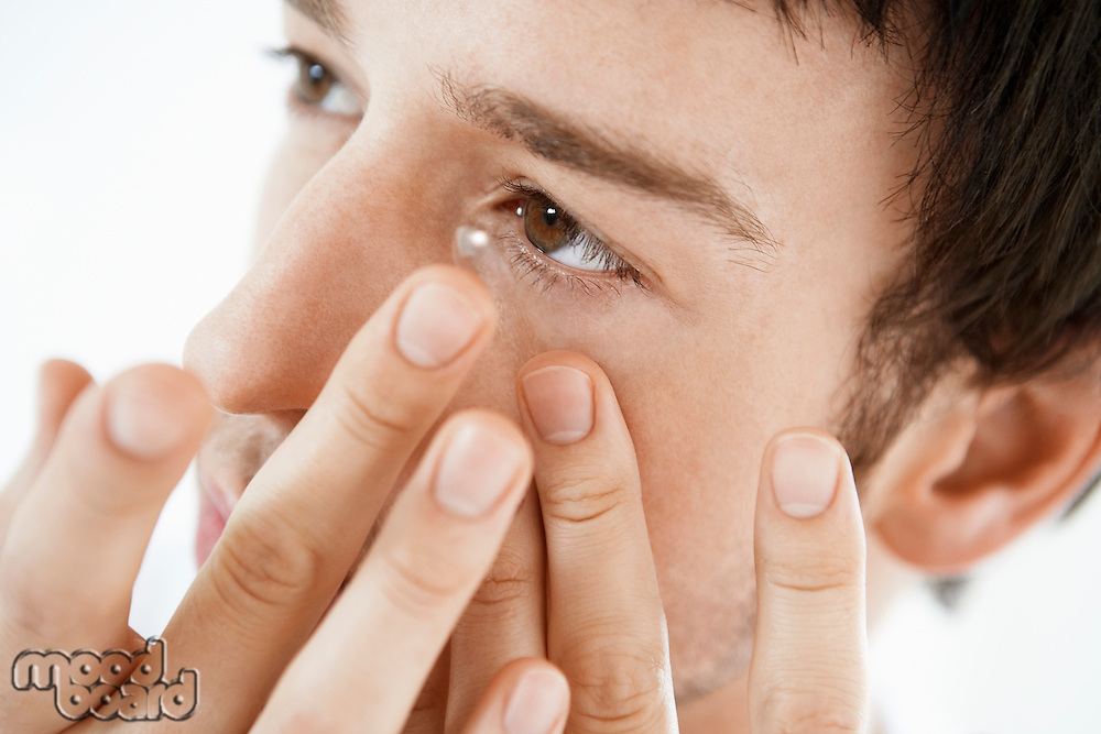 Man inserting contact lens close up