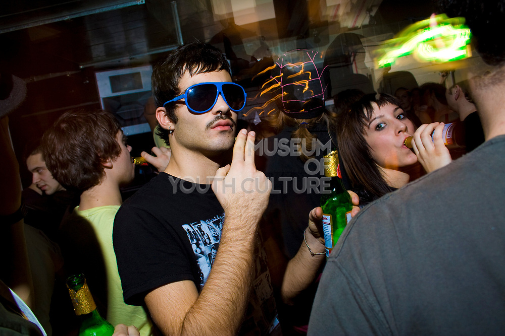Moustached guy in sunglasses motioning for cigarette, T Bar, London.
