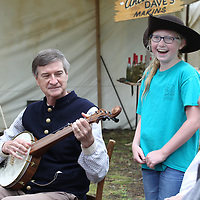 Eliza Whitenton gets to wear Pat Arinder's hat as he play the banjo before Friday's Brice's Crossroads Discovery School Day gets underway.