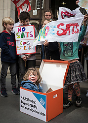 © Licensed to London News Pictures. 03/05/2016. London, UK. Leila, 4, sits in the petition box as parents and children gather outside the Department for Education before handing in a petition to Secretary of State for Education Nicky Morgan demanding that Year 2 SATs be scrapped. Thousands of parents are keeping their children out of school as part of a boycott of the exams. Photo credit: Rob Pinney/LNP