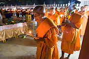 21 FEBRUARY 2008 -- KANCHANABURI, THAILAND: Buddhist monks process around their temple by candlelight on Sangha Day in Kanchanaburi, Thailand. Sangha Day, also known as Magha Puja Day,  commemorates the Buddha's visit to Veruvana Monastery in the city of Rajagaha, when 1,250 arhats are said to have spontaneously returned from their wanderings to pay their respects to the Buddha. Sangha Day is celebrated on the full moon day of the third lunar month which is usually March but fell in February in 2008.   Photo by Jack Kurtz