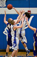 Coeur d'Alene High's Andrew Baracco goes up to block the shot of Riley Beck from Lewiston High as Devon Loy also defends during the second half of the Vikings 74-62 win Thursday.