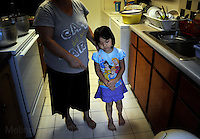 NEW ORLEANS, LA- June 22:  Christine Nguyen, 3, mopes around the kitchen after lunch... The Nguyens', a Vietnamese fishing family, at home in east New Orleans, New Orleans, Louisiana, Tuesday June 22, 2010.  Dung Nguyen, the father, has been unable to work on the shrimp boat  since the spill, and has had to apply for assistance and train for oil spill clean up work. (Melina Mara/The Washington Post)