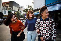 Three young Vietnamese students in the Old Quarter of Hanoi, Vietnam.