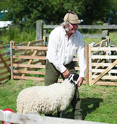 © Licensed to London News Pictures.15/08/15<br /> Rosedale, UK. <br /> <br /> A farmer stands with one of his sheep during an event at the Rosedale Country Show. This mainstay annual event remains as popular as ever attracting visitors and entrants from across the region.<br /> <br /> Photo credit : Ian Forsyth/LNP