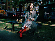 Young woman sitting on park bench with book in hand.
