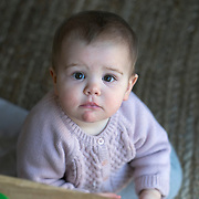 A ten month old baby girl looks directly at the camera while playing. Photo Tim Clayton