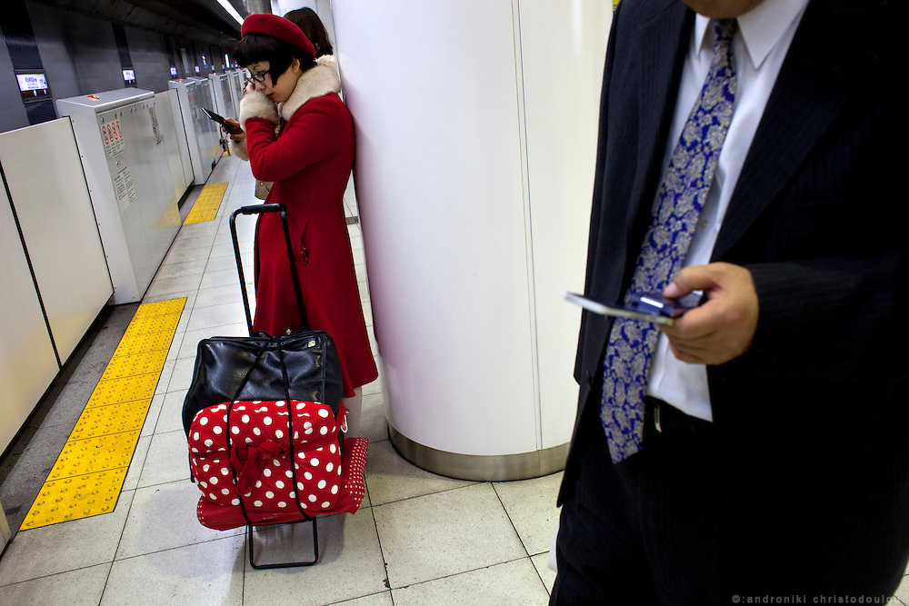 Japanese girl dressed in red waiting for the train on the platform of Fukotoshin line in Harajuku.
