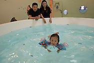 P&eacute;kin, le 16 mai 2014<br /> Ding Libo (le papa), Qi Cong (la maman) regardent leur fille Ding Yuhan, nager dans la piscine d'un centre de loisirs pour enfants.