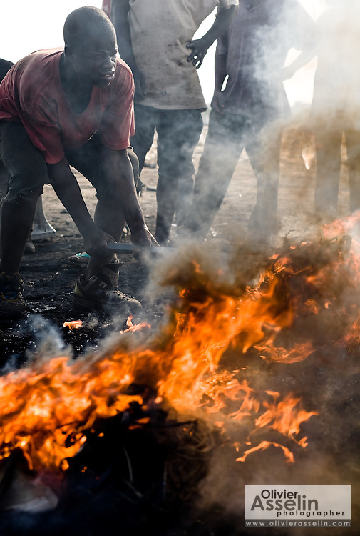 A young man stirs the fire he uses to burn plastic off computer parts to recover copper that he will then sell for money near the Agbogboloshie market in Accra, Ghana on Thursday August 21, 2008.