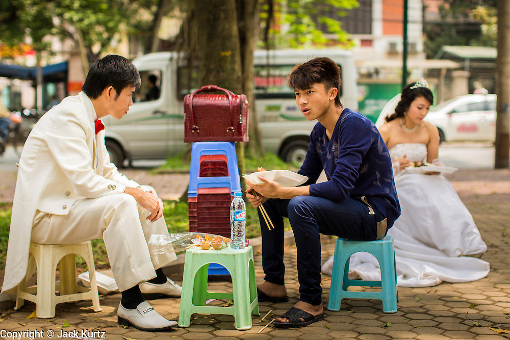 09 APRIL 2012 - HANOI, VIETNAM:  A wedding couple and their photographer's assistant eat lunch in a park before their photo session in Hanoi, the capital of Vietnam. Hanoi, established in 1010 AD, is one of the oldest permanent cities in Southeast Asia. PHOTO BY JACK KURTZ