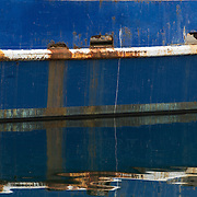 Gloucester, MA USA April, 14, 2015. Reflections of an old fishing trawlter in the harbor.