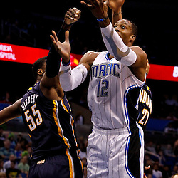 March 11, 2012; Orlando, FL, USA; Orlando Magic center Dwight Howard (12) is fouled by Indiana Pacers center Roy Hibbert (55) as power forward David West (21) defends during the first quarter of a game at  Amway Center.   Mandatory Credit: Derick E. Hingle-US PRESSWIRE