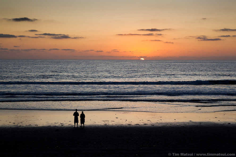 A couple stands on a california beach at sunset.