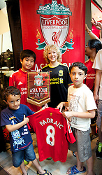 KUALA LUMPUR, MALAYSIA - Friday, July 15, 2011: Liverpool supporters Padraic Dahill from Blundlesands, Wilfred Ho from Kuala Lumpur and Cian and Patrick Nathan from Limerick during a promotional event at the Adidas store at the Mid Valley Shopping Centre on day five of the club's Asia Tour. (Photo by David Rawcliffe/Propaganda)