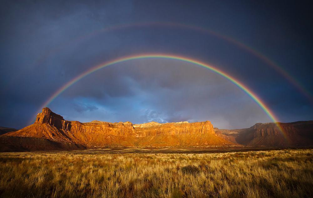 A rainbow and storm clouds over mesas and desert grasslands in southeastern Utah, USA.