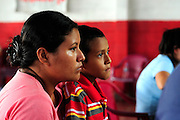 A mother and her son awaiting the results of their medical tests, as part of a series of medical investigations carried out by the 'Nefrolempa' health team into the high incidence of chronic renal failure in the region.<br /> <br /> Community of Nueva Esperanza, Bajo Lempa, El Salvador. 2011.<br /> The 'Nefrolempa' research project is a collaboration between the El Salvador Ministry of Health, the Nephrology Institute of Cuba's Ministry for Public Health and the United Bajo Lempa Committee Association. The aim of the project is to investigate the reasons for the high levels of Chronic Kidney Disease (CKD) suffered by the communities within the Bajo Lempa region. It is exploring whether the use of agrochemicals might be a factor in the prevalence of the disease.<br /> <br /> Medical team: Dr Elsy Brizuela de Jimenez, Directora Unidad de Salud. Miriam Colindres, Nurse. Maria Eraida Velasquez, clinic and laboratory worker. Ecuilia Castro Peraza, Nutritionist. Veronica Contreras, Education for health. Guadelupe Nunez, Psychologist. Luis Diaz General support worker. Dr Raul Herrera Valdes, Nefrologo, Cuba. Dr Miguel Almaguer Lopez, Nefrologo Cuba. Dr Carlos Orantes, Salvadorean Nefrologist. Dr Juan Carlos Awaya, Salvadorean Nefrologist.
