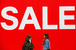 "© Licensed to London News Pictures. 23/12/2018. London, UK. Couple women speaking on the phone in front of a window displaying showing ""SALE"". Last minute Christmas shoppers take advantage of pre-Christmas bargains in London's Oxford Street. Fewer shoppers have been reported shopping in Britain's high streets as online sales increase. Photo credit: Dinendra Haria/LNP"