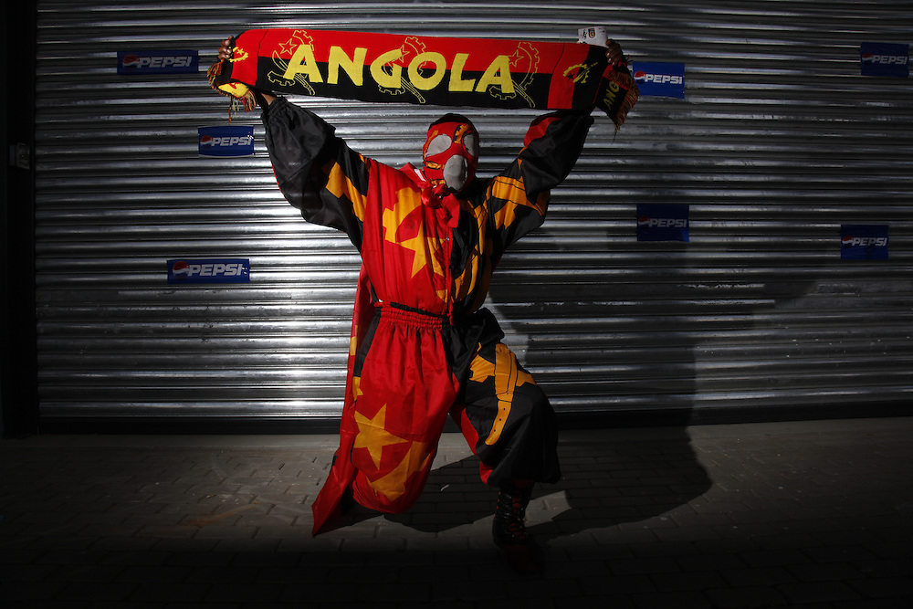 Portrait of Angolan football fan in full Angola costume and face mask holds his Angola flag high.  Ghana V Egypt.The Orange African Cup of Nations Final, Luanda, Angola, Africa. 31/01/2010.www.photoshelter.com/c/lightfootphoto Pictures by Z & D Lightfoot.