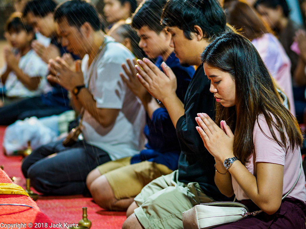 "01 MARCH 2018 - BANGKOK, THAILAND:    People pray as they're sprinkled with blessed water during Makha Bucha Day ceremonies at Wat Pathum Wanaram in central Bangkok. Many people go to temples to perform merit-making activities on Makha Bucha Day, which marks four important events in Buddhism: 1,250 disciples came to see the Buddha without being summoned, all of them were Arhantas, or Enlightened Ones, and all were ordained by the Buddha himself. The Buddha gave those Arhantas the principles of Buddhism. In Thailand, this teaching has been dubbed the ""Heart of Buddhism.""    PHOTO BY JACK KURTZ"