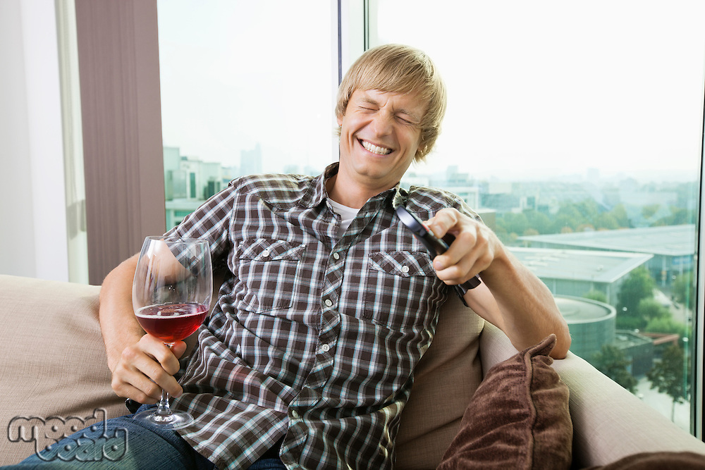 Cheerful mid-adult man with wine glass watching television on sofa at home