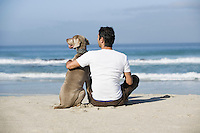 South Africa Cape Town Man and dog sitting beach