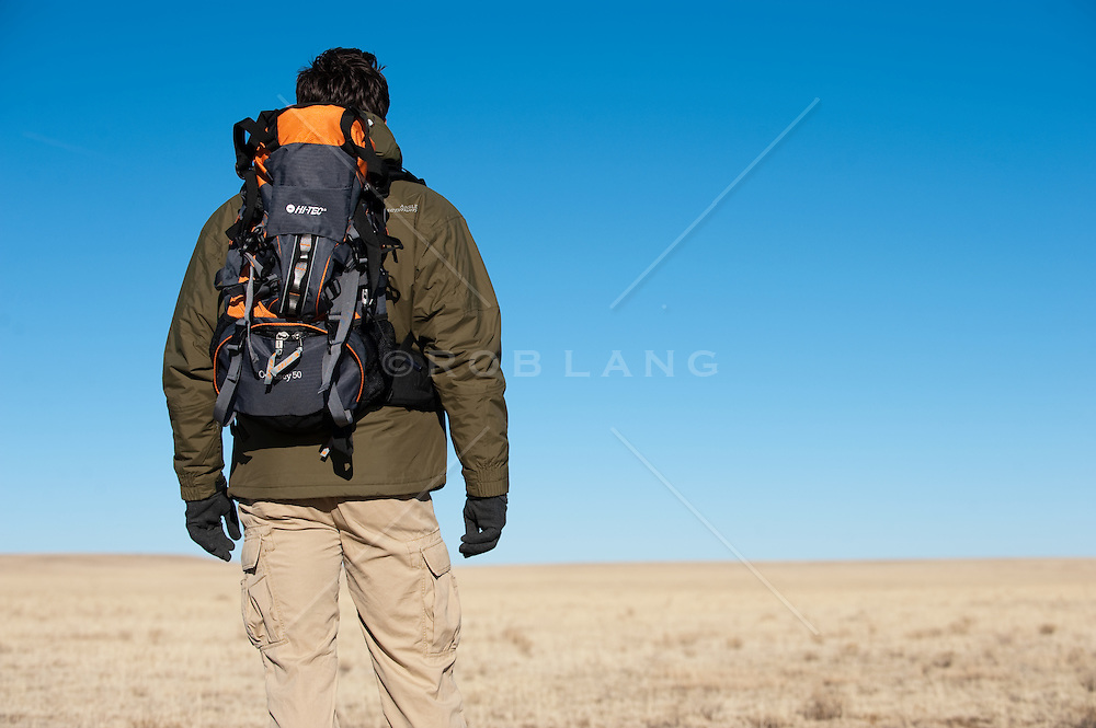 Backpacking man looking out on an empty grass covered high desert expanse