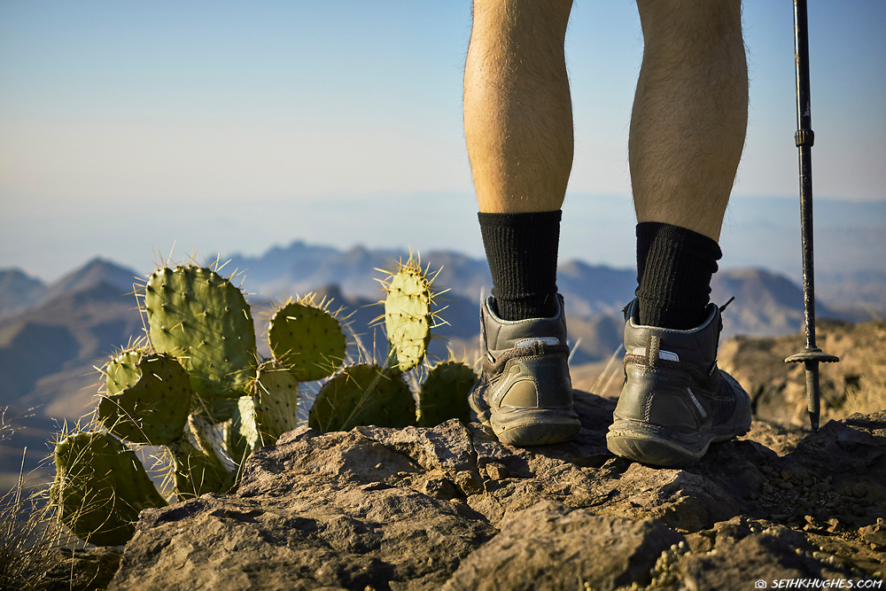 Close up of hiking boots and cactus overlooking a desert mountain landscape. South Rim, Chisos Mountains, Big Bend National Park, Texas