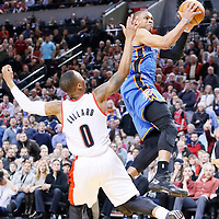04 December 2013: Oklahoma City Thunder point guard Russell Westbrook (0) goes for the layup past Portland Trail Blazers point guard Damian Lillard (0) during the Portland Trail Blazers 111-104 victory over the Oklahoma City Thunder at the Moda Center, Portland, Oregon, USA.