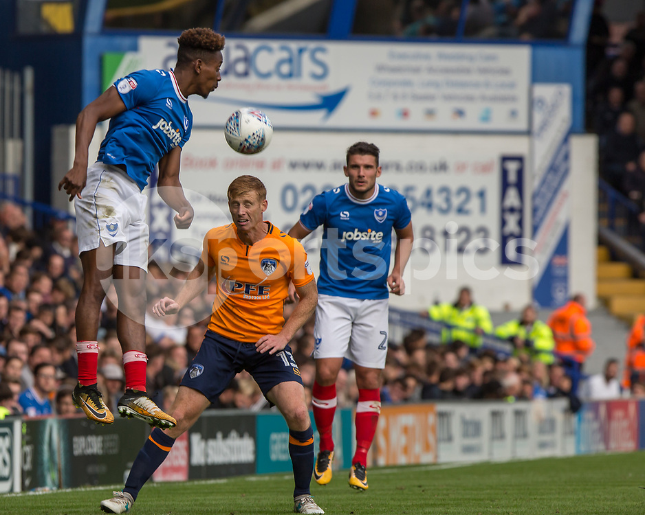 Jamal Lowe of Portsmouth rises above Eoin Doyle of Oldham Athletic during the EFL Sky Bet League 1 match between Portsmouth and Oldham Athletic at Fratton Park, Portsmouth, England on 30 September 2017. Photo by Simon Carlton.