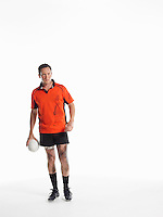Rugby player standing holding ball