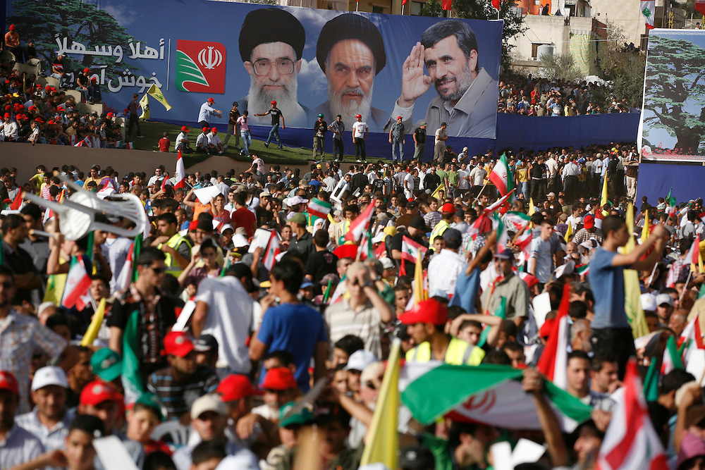 On the second and final day of his visit to Lebanon, Iranian President Mahmoud Ahmadinejad traveled to the southern town of Bint Jbeil. There a Hizballah-organized rally was held to welcome Ahmadinejad to the south Lebanon, an area where Hizballah is widely supported. Tens of thousands gathered for hours holding flags of Iran, Hizballah, Lebanon and other political parties, cheering the Iranian president as he arrived by helicopter from Beirut. ///A sign at the stadium in Bint Jbeil shows Iranian President Mahmoud Ahmadinejad along with Ayatollahs Khomeini and Khameinei, Iran's past and current Supreme leaders respectively.