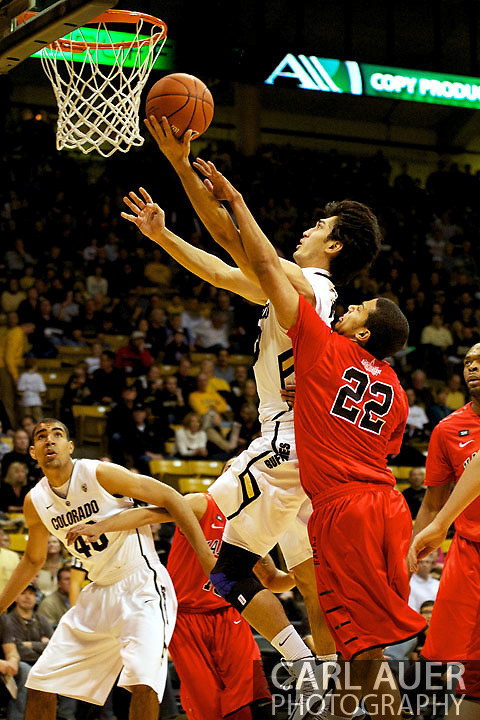 December 29, 2012: Colorado Buffaloes senior guard SABATINO CHEN (23) is fouled by University of Hartford Hawks freshman guard EVAN COOPER (22) as he slices through the key for a shot in the NCAA Basketball game between the University of Hartford Hawks and the Colorado Buffaloes at the Coors Event Center in Boulder Colorado