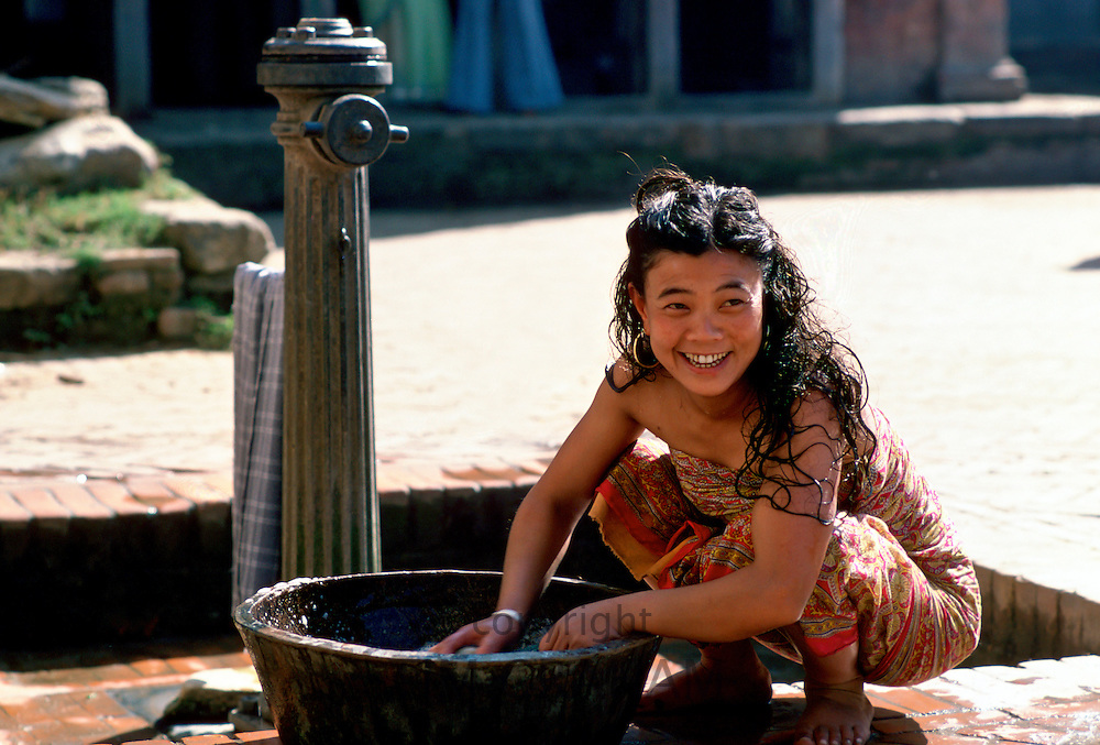 Young woman washing at water pump, Patan, Nepal