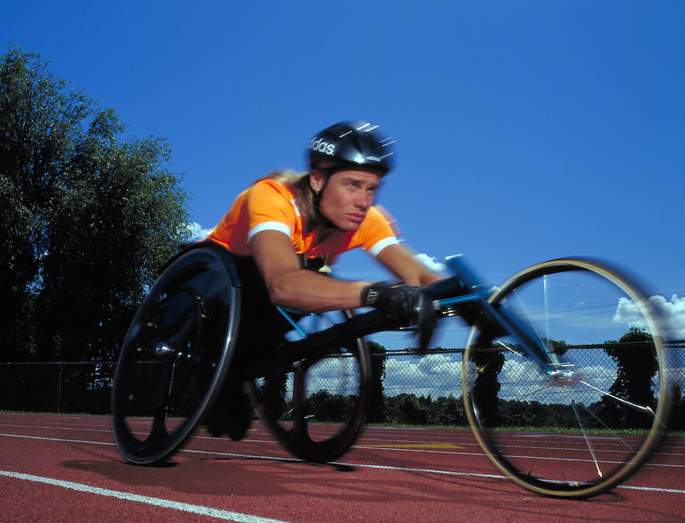 Young man races a wheelchair on track
