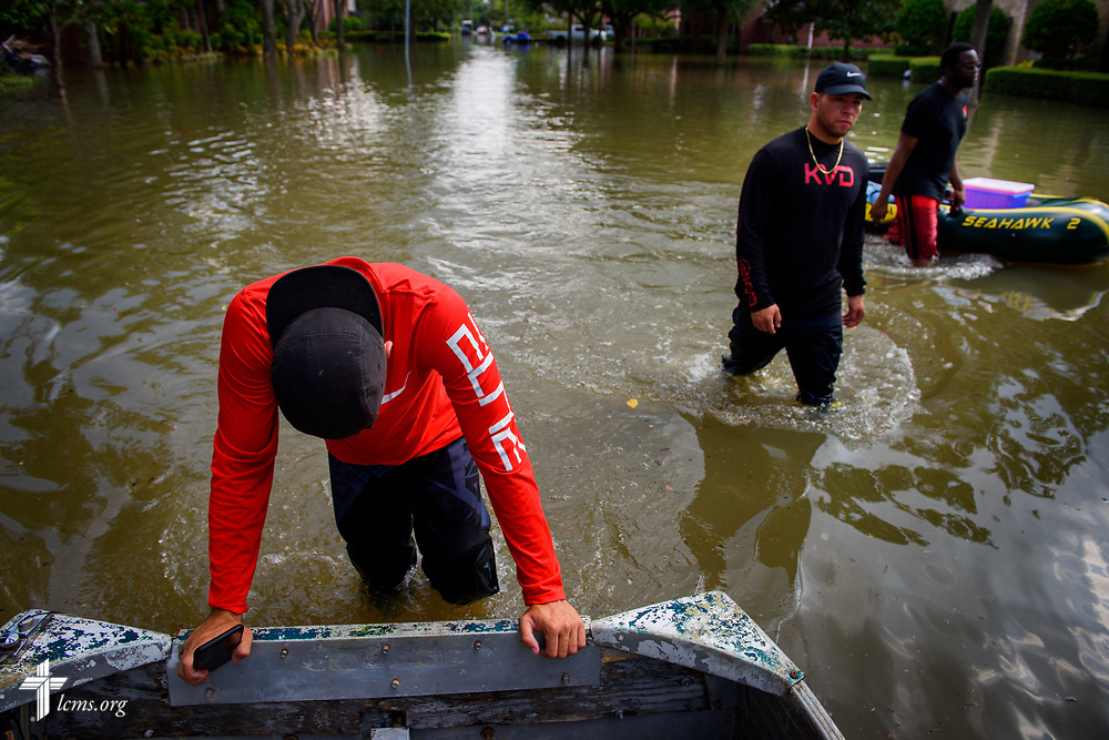 Volunteers from Miami help push a boat down a flooded road in Houston on Monday, Sept. 4, 2017. LCMS Communications/Erik M. Lunsford