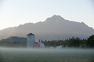 Morning mist partially obscures a barn and silo in Palmer, Alaska.
