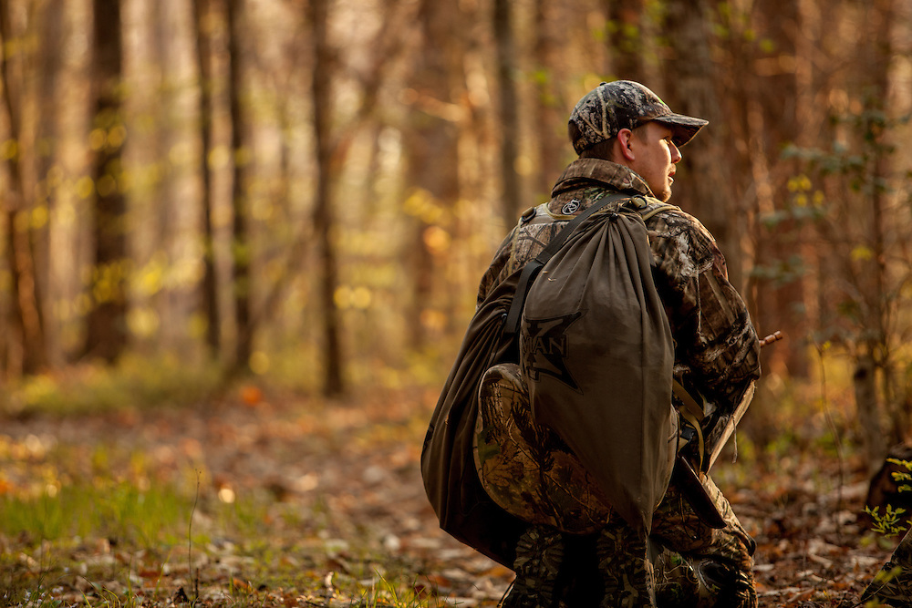 Lone hunter walking through woods listening for gobblers.
